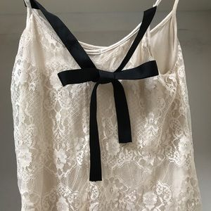 Cream colored tank with black bow on back